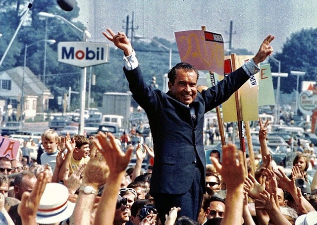 Richard Nixon standing at a Victory parade waving Victory hands. I am not a crook. marchmatron.com