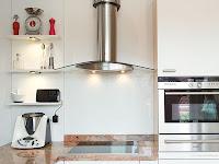 Hinter dem Kochfeld ist ein Spritzschutz aus Glas eine praktische und schöne Lösung