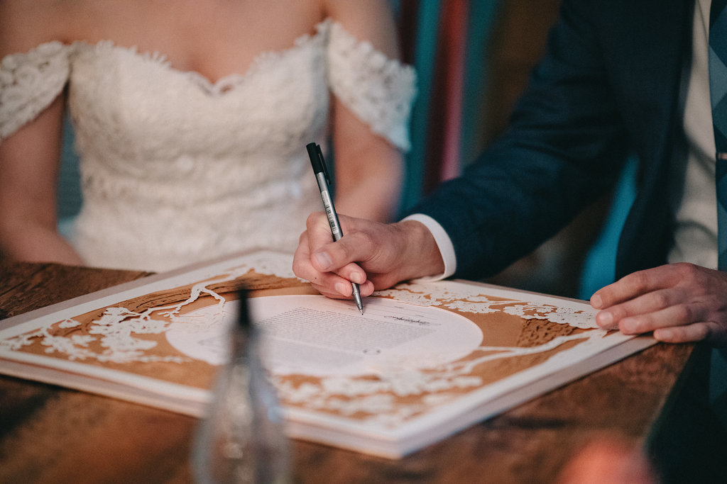 Signing the ketubah; wedding photos by The Spragues