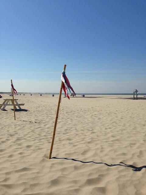 Paal met vlaggetjes met daarachter het strand en in de verte de zee