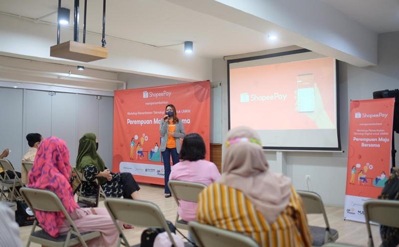 Eka Nilam Dari, Head of Strategic Merchant Acquisition ShopeePay memberikan penjelasan pada seorang wirausaha perempuan untuk memaksimalkan layanan pembayaran digital
