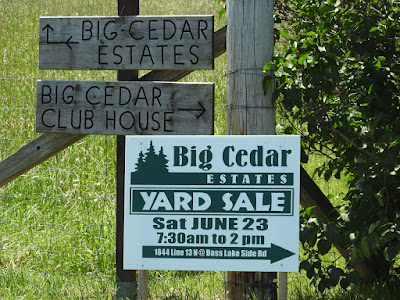 Directional signs to the Big Cedar clubhouse and community, and a large green and white sign proclaiming their yard sale dates and time.
