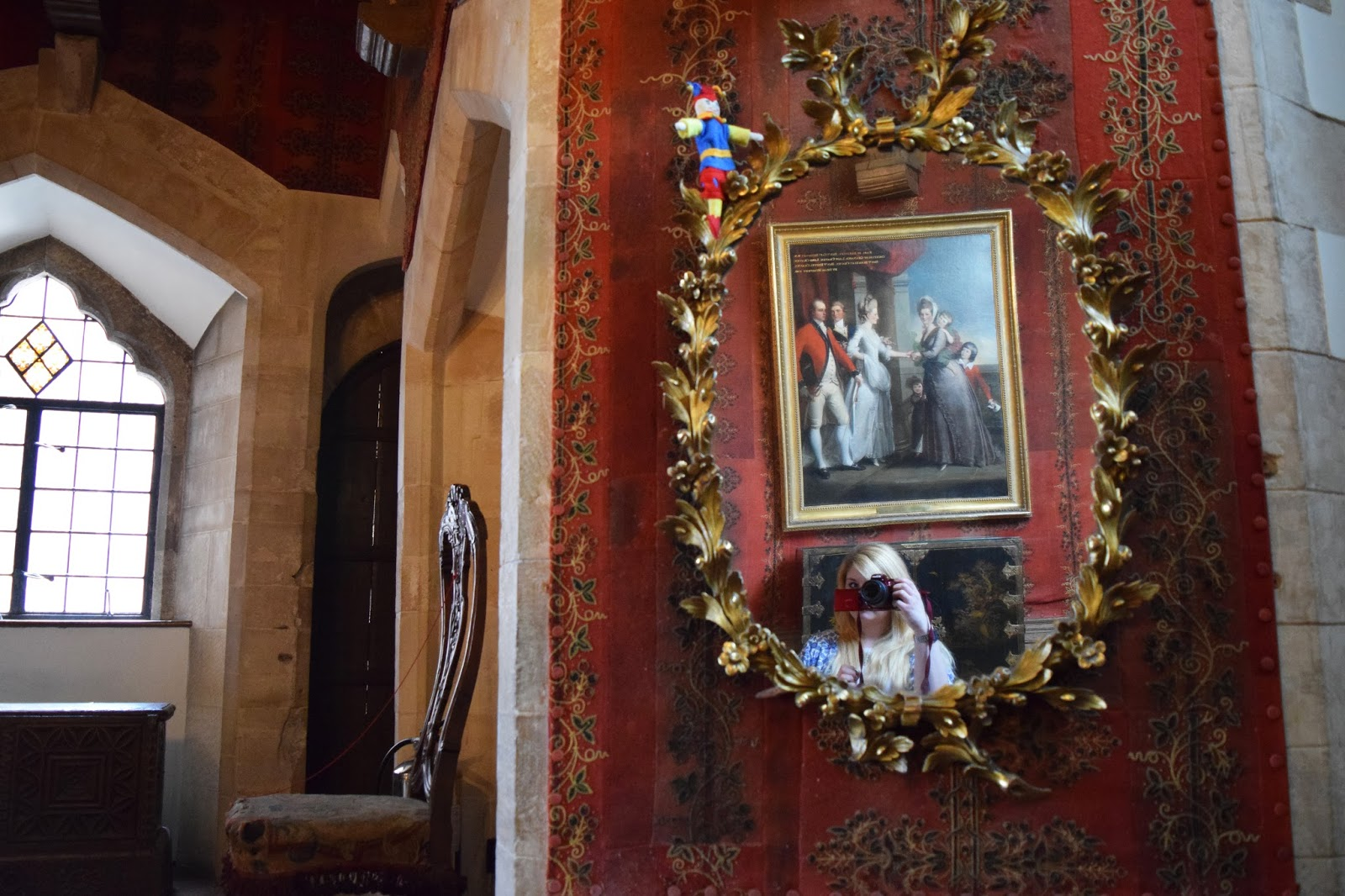 inside a hallway in Berkeley Castle. a gold ornate mirror can be seen and inside this myself taking a selfie. to the side of the mirror is an old chair below a window