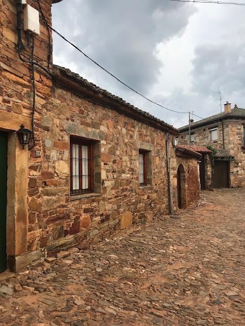 Rincón del pueblo de Castrillo con la calle y las fachadas de piedra rojiza