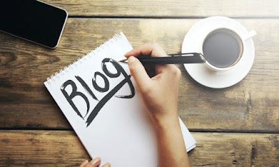 Mano escribiendo la palabra blog sobre un trozo de papel en un escritorio de mesa