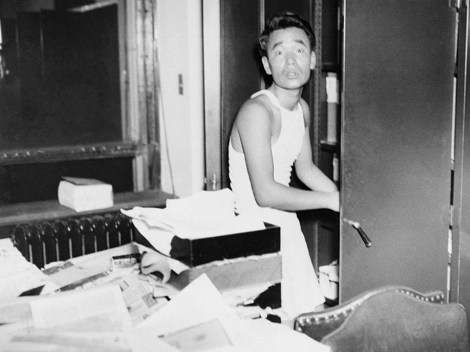 This unidentified Japanese man turns to face a visitor at the Japanese Consulate in Chicago, on December 9, 1941. Clad only in underwear, he was startled while in the act of taking papers and files from a cabinet. Confidential papers at the consulate had been burned.