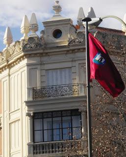 La bandera izada sobre un mástil ondea ante un edificio histórico.