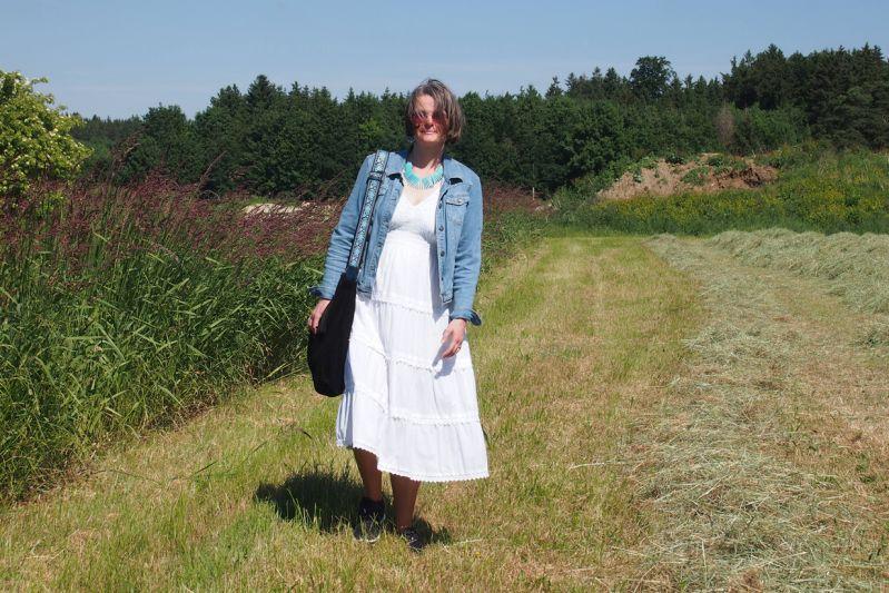 Weißes Sommerkleid mit schwarzen Sneakern und Jeansjacke kombiniert.
