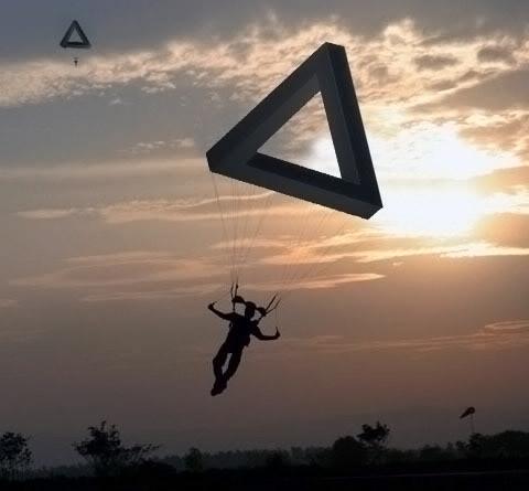 Üçgen paradoks şeklindeki bir paraşütle iniş yapan bir adam