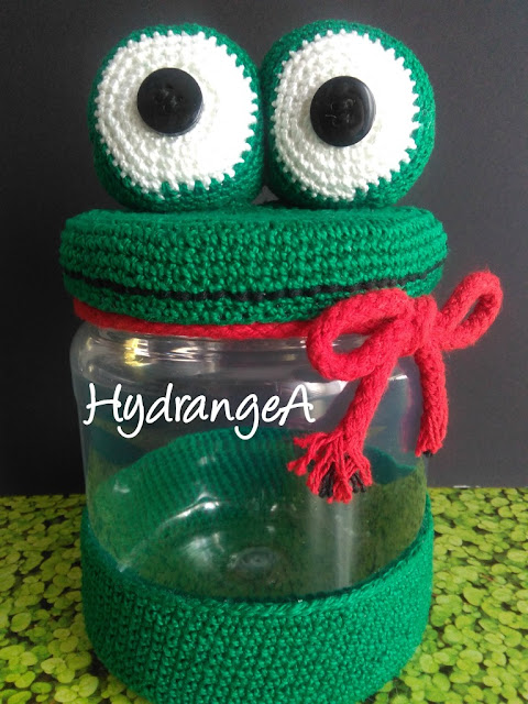 Dulcero de bote de plástico reciclado, con adorno en crochet de una rana en color verde