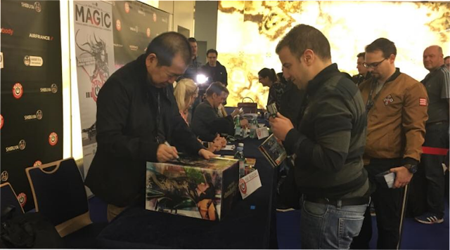Yu Suzuki signs the box of a Lan Di figure for a fan.