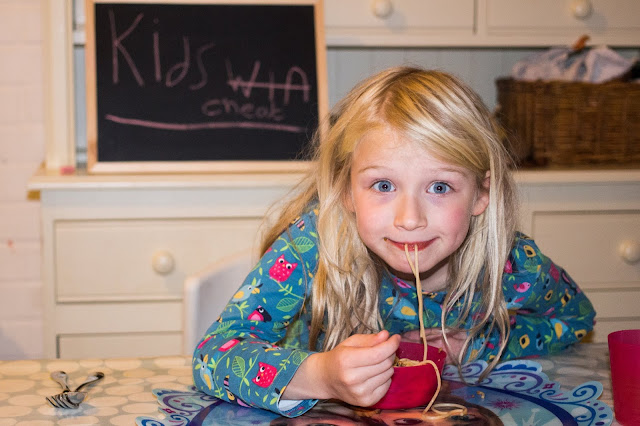 "A girl eating spaghetti. Chalk board in background has win crossed out and cheat written instead so it says ""Kids Cheat"""