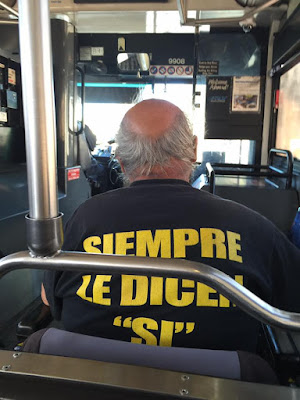A man wearing a t shirt with yellow writing sits in his electric scooter on a bus.
