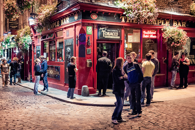 A night time picture at the corner of The Temple Bar Pub in Temple Bar with a few people outside socialising