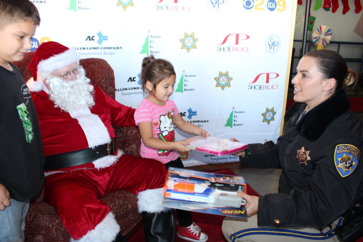 chp officer siara lund gives children toys with santa at the chips for kids toy giveaway