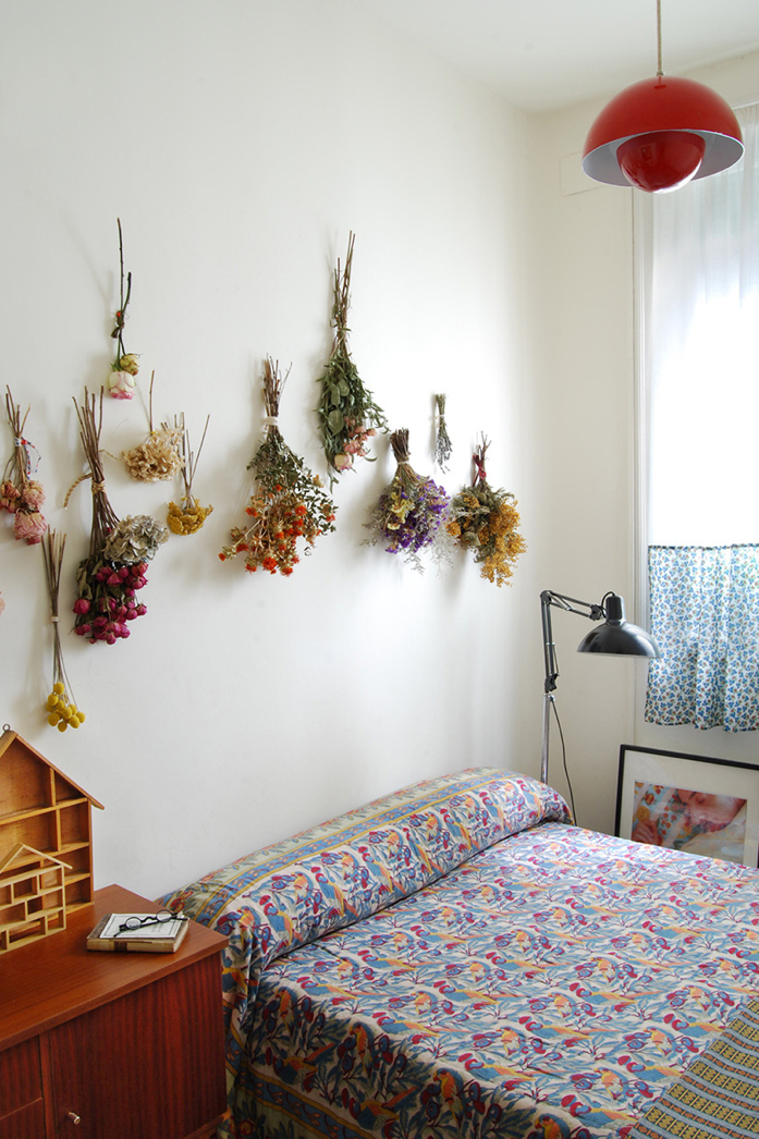 A row of dried flowers above the bed adds wow factor in this bedroom