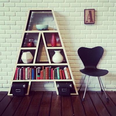 Modern doll's house bookcase in the shape of a letter A, filled with books and ornaments.
