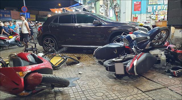 Nhiều xe máy nằm ngổn ngang trên vỉa hè, Đầu chiếc Mercedes vỡ bung sau khi tông vào cửa hàng điện thoại