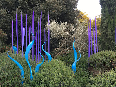 bright blue and purple glass 'reeds' and 'leaves' in a garden bed