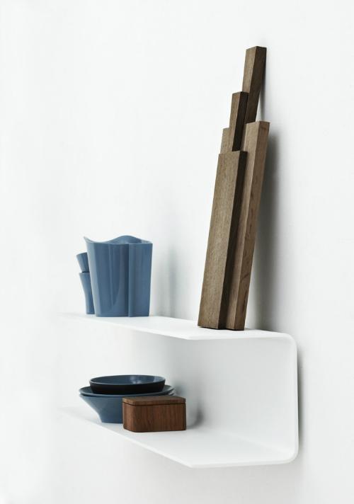 Das weiße Regal in U-Form ist schön mit dunklen Holzbrettern und blauen Schalen dekoriert