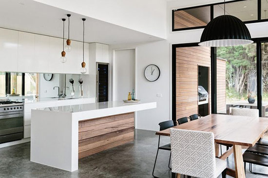 Phòng bếp tối giản màu trắng tinh tế và góc ăn hiện đại được kết nối bằng màu sắc và những chiếc đèn treo.