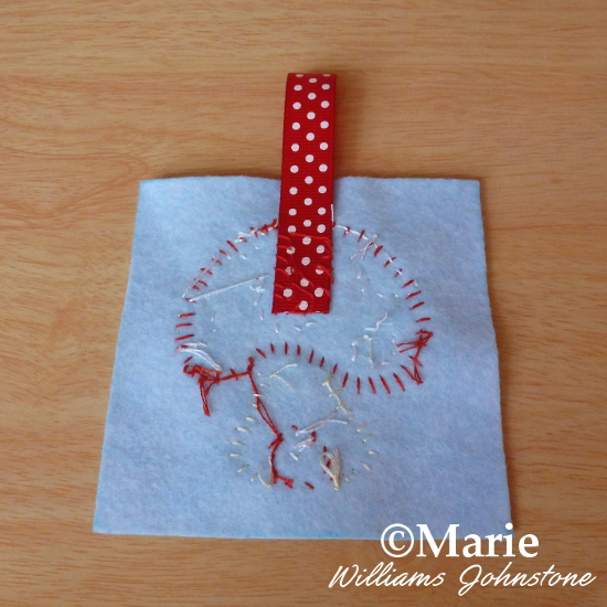 Adding a loop of red polka dot ribbon to the reverse front of the pincushion
