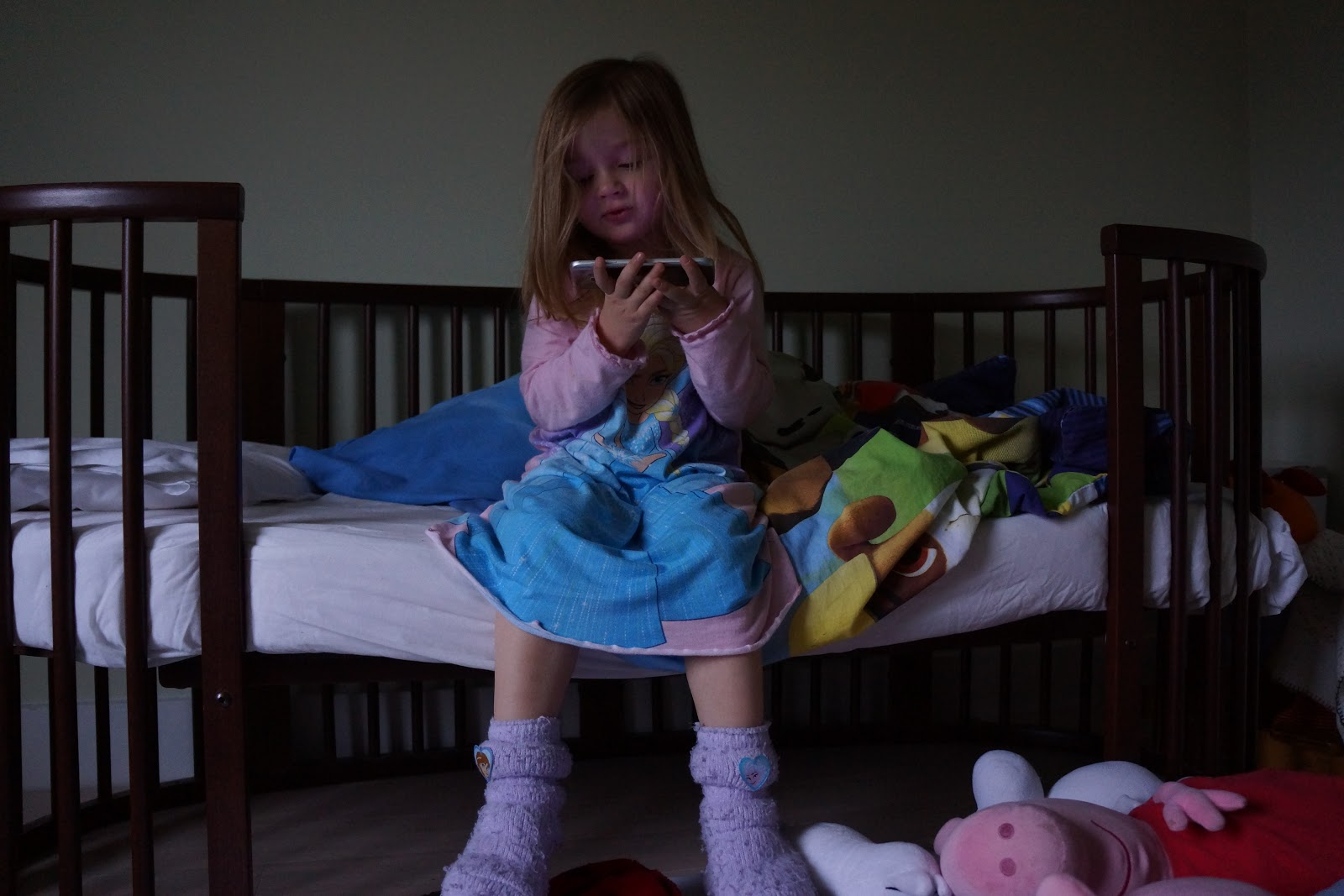 toddler girl sitting on bed watching a mobile film