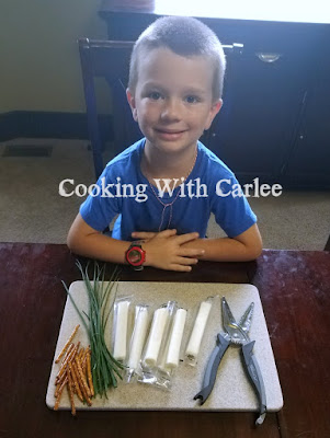 kid with cutting board of ingredients to make broomsticks