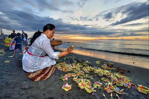 Bali, offerte agli spiriti su una spiaggia al tramonto