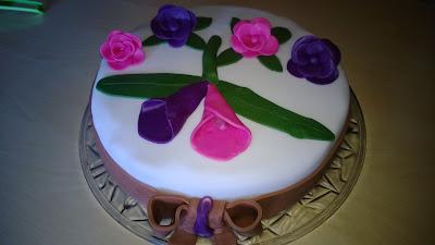 Torte mit Weißen Rollfondant überzogen und Pink/ Lila Blüten als Deko