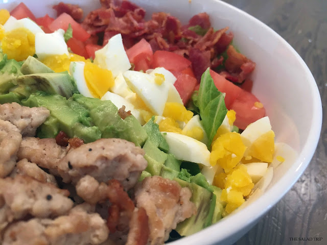 Close up of ground chicken, avocado, eggs, tomatoes and bacon
