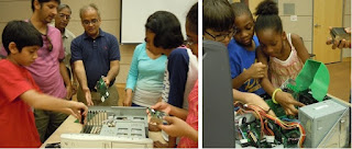 Group of children examining a computer parts and a dismantled computer