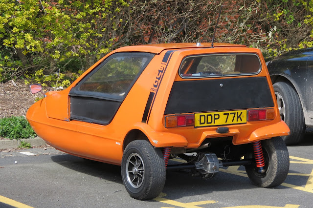 Orange, three-wheeled 1960s car in a car park.