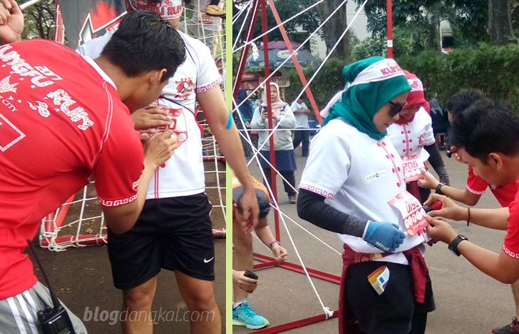 Peserta wajib dicap atau distempel sebagai tanda lulus melalui rintangan saat lari Kungfu Run 2017 Daan Mogot City.