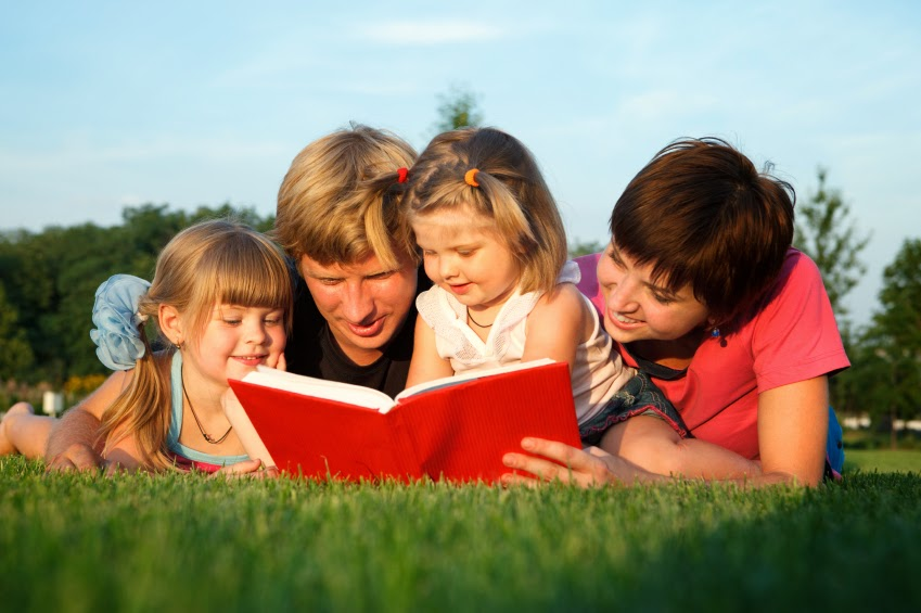 NAMC montessori summer learning ideas follow the child. Family reading on grass