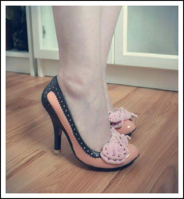 side angle of feet wearing Irregular Choice peach coloured Take A Bow shoes