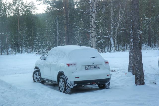 Carro coberto de neve entre árvores em em Ivalo, Finlândia