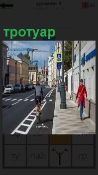 На дороге едут машины а по тротуару двигаются пешеходы. Велосипедист на специальной дорожке едет