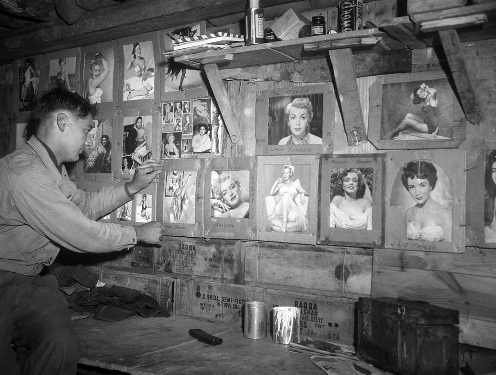 Pfc. Milton Reince of Green Bay, Wisconsin, adds a picture of Mitzi Gaynor to his bunkerful of pinups at his post in Korea on December 18, 1952.