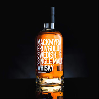 A bottle of Mackmyra Gruvguld Swedish Single Malt Whisky set against a black background