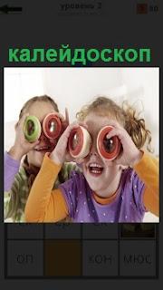 Две девочки приложили к глазам цветной калейдоскоп и внимательно рассматривают внутри