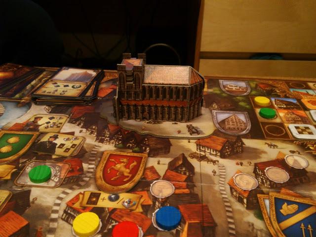 Günter Burkhardt. Do tej pory nie znałem tego nazwiska w świecie gier planszowych i nie miałem pojęcia co autor może zaproponować. Jego największy sukces to gra o zbieraniu herbaty, Darjeeling, która nie zyskała sympatii graczy, nie przebijając się do wyższych pozycji w rankingu BGG. Tym razem może być o wiele lepiej, bo Burkhardt postanowił stworzyć grę o pięknym i malowniczym, niemieckim mieście Ulm. Jego wspaniała katedra jest wizytówką miasta, a teraz także i gry Ulm. Zapraszam na recenzję.  Wszystkie elementy gry, które możecie znaleźć w pudełku obejrzycie w UNBOXINGU, na który Was serdecznie zapraszam. Jest tego naprawdę sporo, zaczynając od dwóch arkuszy instrukcji, sporej liczby żetonów, kart i drewnianych znaczników. Całości dopełnia genialna, składana katedra, która nie ma co prawda ważniejszej funkcji w grze, ale wizualnie prezentuje się znakomicie. Ostrząc zęby na wydanie międzynarodowe trzeba wydać około 140 złotych, co jest zbyt wysoką ceną, zwłaszcza, że w komplecie dostaniecie dwie talie kart w różnych językach. Na szczęście, Ulm już wkrótce pojawi się na polskim rynku, dzięki wydawnictwu Sharp Games, które wyda grę tylko i wyłącznie w naszym rodzimym języku.    Zasady opisane w instrukcji wyglądają przejrzyście i klarownie, Problemy pojawiają się w momencie, gdy trzeba je wytłumaczyć innym. Musicie posiłkować się planszą, kartami, opisywać wszystko po kolei. W głównej mierze to wina mnogości akcji oraz ich budowy, które przy słuchaniu zasad mogą się zlewać i kompletnie pomieszać. Zalecam rozegrać pokazową rundę, z wykorzystaniem wszystkich znaczników oraz akcji, tak by nie było żadnych wątpliwości.    Przygotowanie do gry jest bardzo proste. Każdy z graczy otrzymuje znaczniki w swoim kolorze, 3 pieczęcie rodowe, dwie monety, jeden żeton Wróbla (symbolu Ulm) oraz losowy dobrany żeton akcji. Swoje barki ustawiamy na polach startowych, jeden z kolorowych znaczników kładziemy na torze punktacji na polu nr 5. Najważniejszym miejscem w grze Ulm jest szach
