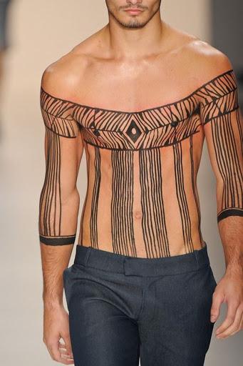 Uma série de linha que faz com que pareça que este modelo está vestindo uma shoulderless blusa é processado neste confuso tatuagem.