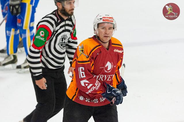 Hokejista portrets ar spēles tiesnesi fonā