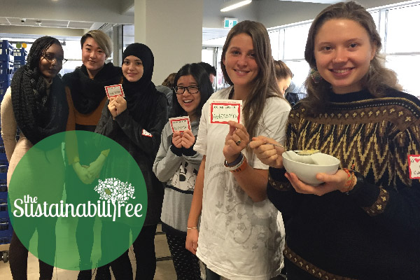 A group of volunteers pose for a picture with the stickers they distribute to zero waste diners