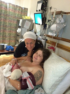 A new mother (author Meagan Flaherty) cradles her newborn skin-to-skin soon after delivering poses fpr a picture with Leslie Cuffee (doula)
