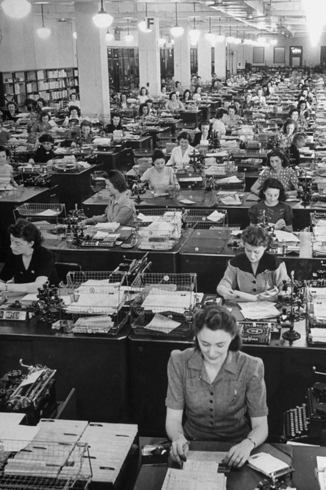 325 American women working to fill mail orders in the office of the Book of the Month Club. The women wear a wide variety of blouses and dresses, including decorative patterns and polka dots, though most have V-necks. Some wear brooches. They typically wear shoulder-length hair; some, as the woman at the front, use hair nets. 1942.