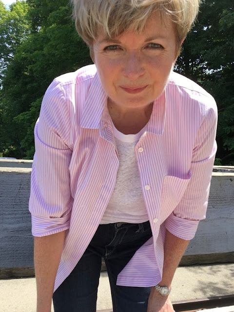 close up of woman in pink striped shirt, white tee and jeans