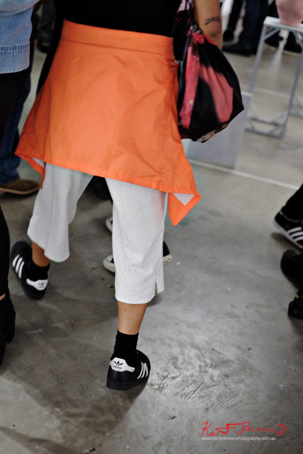 orange fluro jacket around waist, white pants black Adidas 'Rome' runners. Spring Fashion Ambushed by Street Fashion Sydney. Photographed by Kent Johnson.