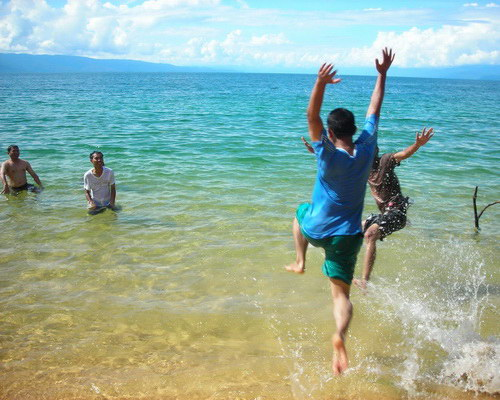 Travel.Tinuku.com Lake Poso white golden sandy beach and green blue water surrounded by hills and orchids forest